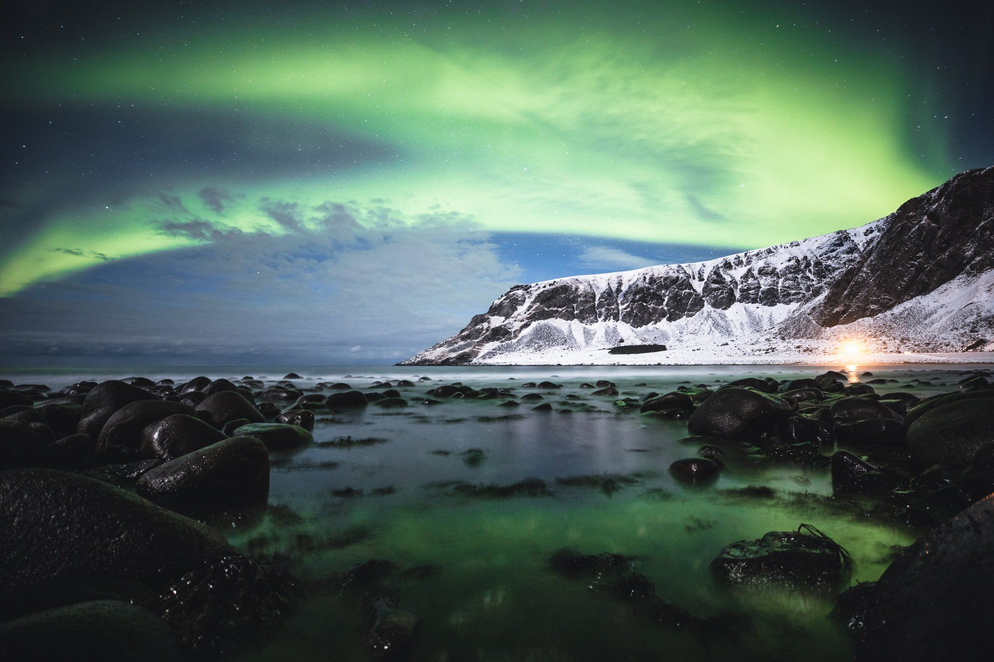 The Northern lights illuminate the sky, casting green reflections in the lake below.